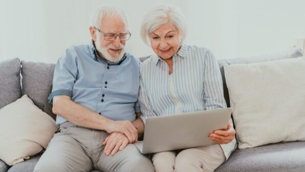Elderly couple with computer laptop at home